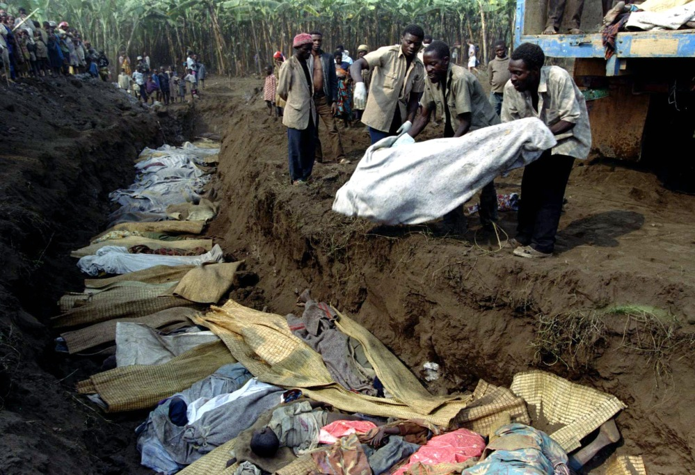 Volonteers throw more refugee bodies out of a truck into a mass grave, July 20th. Rwandan refugees w..